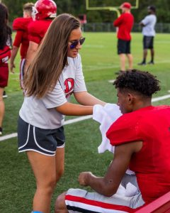 1fbe88434f69 Freshman student trainer Clohe  Wall dabs ice water on a football player s  face during a Diboll High School junior varsity football game at Lumberjack  ...